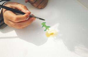 024 Odlarkverkstad. Vide Björling tar vid där han slutade senast och fortsätter måla färdigt sin Ringblomma.