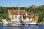 Old cottage with a jetty and boats in the Swedish archipelago